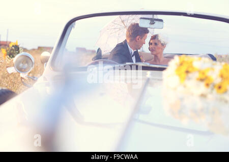 Mariée et le marié dans une voiture ancienne Banque D'Images