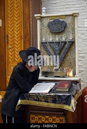 Un jeune juif religieux de la lecture d'un livre sur le podium dans une synagogue à Crown Heights, Brooklyn, New Banque D'Images