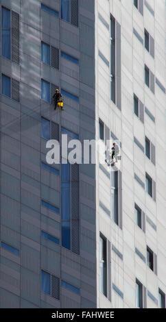 La descente en rappel de produit lave-vitre en plein travail sur un immeuble de l'East End de Londres UK Banque D'Images