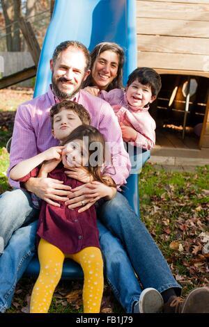 Famille dans une ligne entre les jambes des uns et des autres sur l'aire de glisse, smiling at camera Banque D'Images