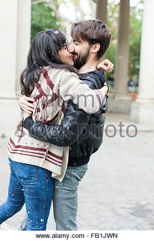 Jeune couple hipster couvert de confettis hugging in park, Brooklyn, New York, USA Banque D'Images