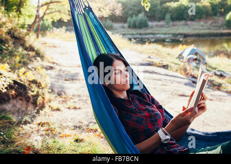 Young woman reading book while lying on hammock in forest Banque D'Images
