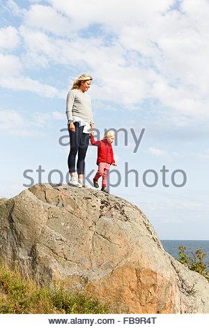 La Suède, l'archipel de Stockholm, Sodermanland, Oja, Woman standing with son (2-3) sur le rocher sous ciel avec Banque D'Images