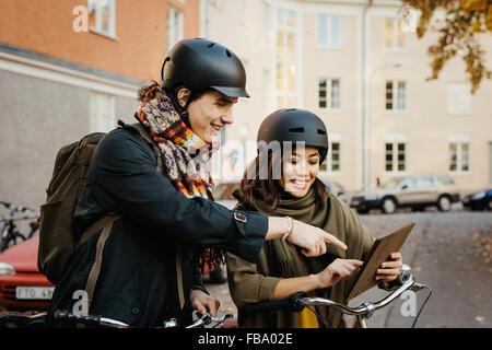 La Suède, l'Uppland, Stockholm, Vasastan, Rodabergsbrinken, deux jeunes gens looking at digital tablet smiling Banque D'Images