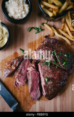 Fabrication d'Angus Ribeye Steak avec des frites, de la moutarde et au raifort Banque D'Images