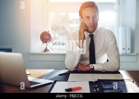 Jeune homme d'affaires blanc à parler au téléphone, assis à 24 portant costume et cravate Banque D'Images