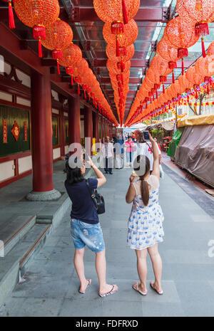 Les personnes qui prennent des photos des lanternes rouges au Buddha Tooth Relic Temple pendant le Nouvel An chinois Banque D'Images