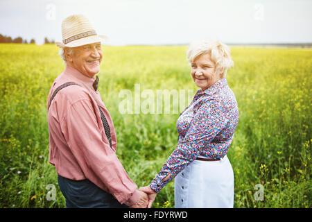 Les aînés affectueux par holding hands while standing in meadow Banque D'Images