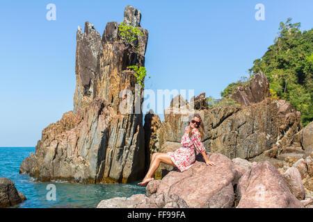 Belle femme parmi les falaises côtières sur l'île de Ko Chang, Thaïlande. Banque D'Images