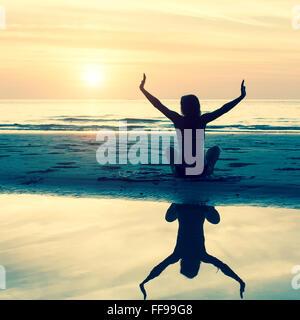 Jeune femme silhouette exercices de yoga sur la plage au coucher du soleil. Banque D'Images