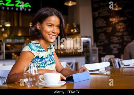 Mixed Race woman se trouve dans cafe en utilisant ordinateur Banque D'Images