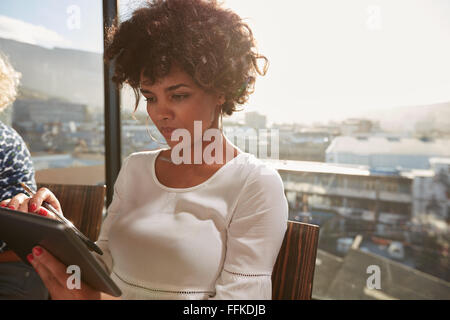 Portrait of young African woman using digital tablet. Attractive businesswoman surf sur internet son tablet Banque D'Images