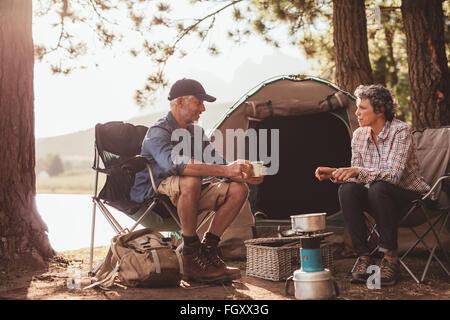 Portrait of happy mature campeurs enjoying coffee par le lac. D'âge mûr se détendre à leur camping. Banque D'Images