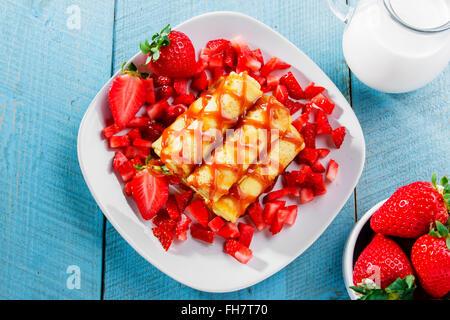 Crêpes roulées avec fraises et petit-déjeuner au caramel Banque D'Images