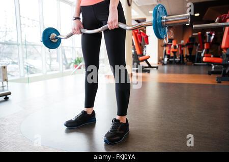 Libre de jambes de jeune femme et de l'exercice permanent de l'athlète avec barbell in gym Banque D'Images