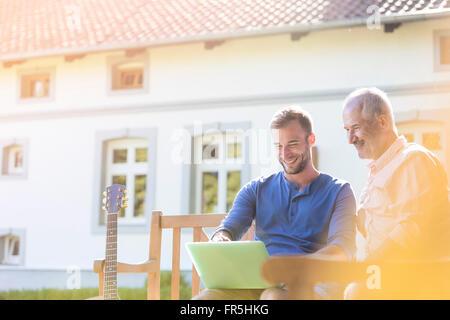 Père et fils à l'aide de l'ordinateur portable sur banc de jardin Banque D'Images