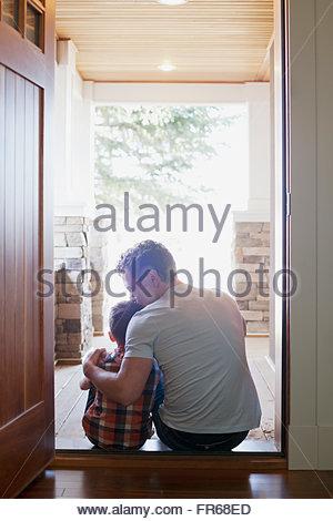 Père et fils assis dans la porte Banque D'Images