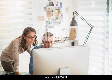 Au bureau, deux jeunes collègues travaillant sur un projet sur un ordinateur, le bureau est moderne et lumineux. Banque D'Images