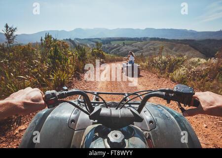 Vue d'un quad dans la nature. Femme devant la conduite hors route sur un véhicule tout terrain. POV'image d'un quad Banque D'Images