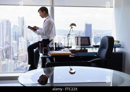Adult businessman sitting on desk in office moderne et la lecture des nouvelles sur tablet pc. L'homme travaille Banque D'Images