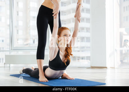 Jolie rousse jeune femme faisant des exercices d'étirement avec un entraîneur personnel Banque D'Images