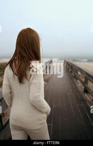 Femme marche sur trottoir de bois at beach Banque D'Images