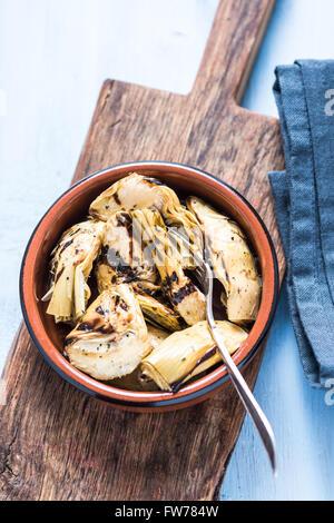 Artichauts cuits au feu dans Bol en céramique, d'en haut sur planche de bois. Banque D'Images