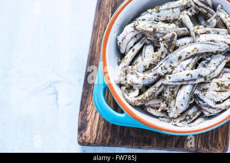 Avec des herbes anchois dans un bol en céramique, de tapas sur planche de bois frais généraux Banque D'Images