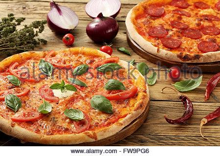 Pizza Margherita et pepperoni sur fond rustique Banque D'Images
