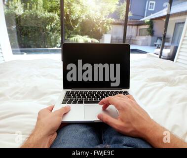 Libre de droit de l'homme étendu sur un lit de travailler sur un ordinateur portable. Shot POV de l'homme dans la Banque D'Images