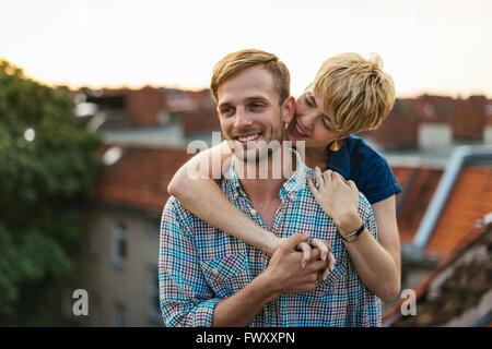 Allemagne, Berlin, Young couple hugging on au coucher du soleil sur le toit Banque D'Images
