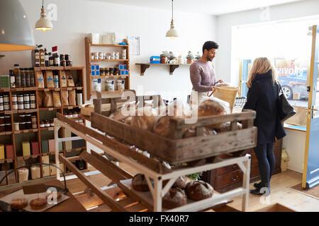 Adjointe aux ventes de sexe masculin féminin au service client en épicerie fine Banque D'Images