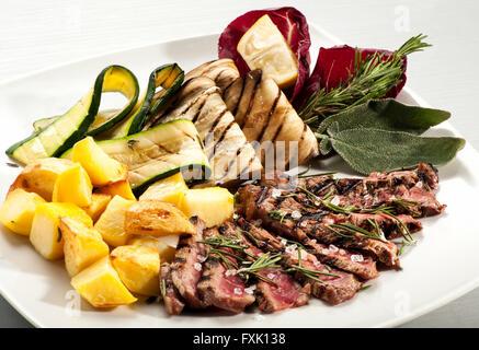 Seule portion de steak cuit rares, des tranches de pommes de terre jaune, aubergine et de squash avec des herbes Banque D'Images