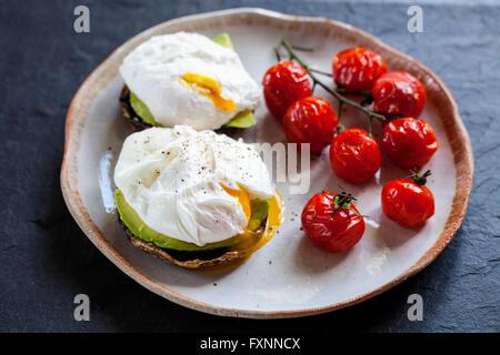 Le petit-déjeuner, les champignons avec de l'avocat et œufs pochés et faites rôtir les tomates cerise sur la vigne Banque D'Images