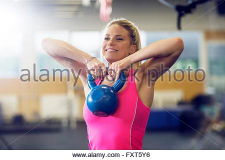 Jeune femme en salle de fitness kettlebell de levage Banque D'Images