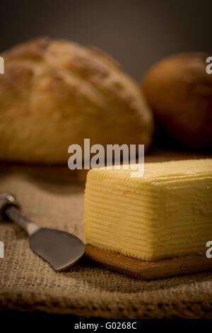 Beurre baratté à la main sur des palettes de bois avec couteau à beurre et du pain. Banque D'Images