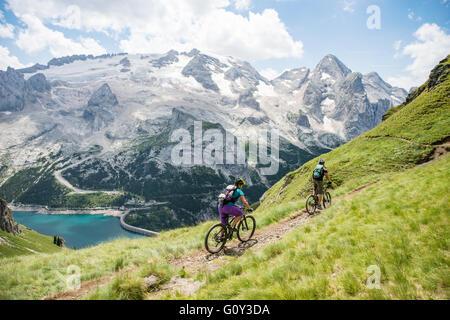 L'homme et la femme mountain biking Glacier Marmolada, Dolomites, Italie Banque D'Images