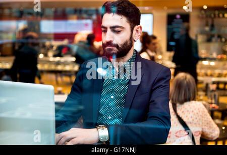 Businessman sitting in cafe siège de fenêtre typing on laptop Banque D'Images