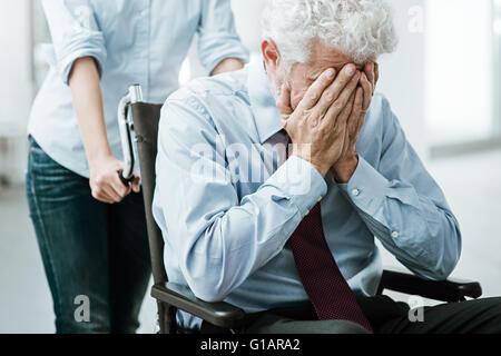 Triste homme déprimé en fauteuil roulant avec la tête dans les mains, une femme prend soin de lui Banque D'Images