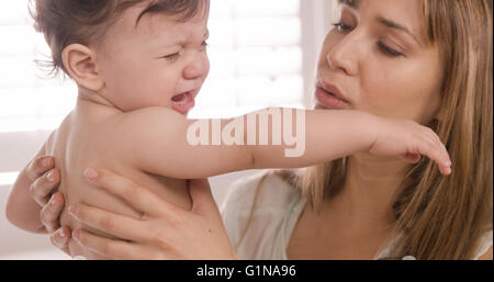 Mère portant son bébé pleurer Banque D'Images