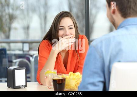Femme couvrant sa bouche pour cacher sourire ou mauvaise haleine pendant une date dans un café avec une fenêtre Banque D'Images