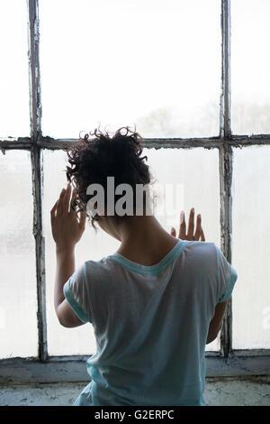 Vue arrière d'une jeune femme debout près de la fenêtre les mains de toucher le verre Banque D'Images