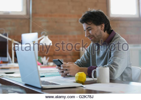 Designer texting with cell phone at desk in office Banque D'Images
