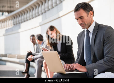 Corporate businessman using laptop on bench outdoors Banque D'Images