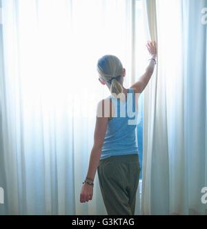 Vue arrière du girl peering through fenêtre rideaux net Banque D'Images