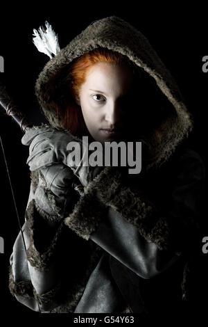 Archer en fille un costume avec bow isolés dans un fond sombre Banque D'Images