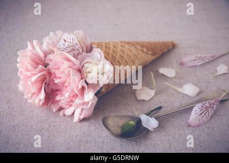 Fleurs oeillet rose dans la crème glacée cornet gaufré Banque D'Images