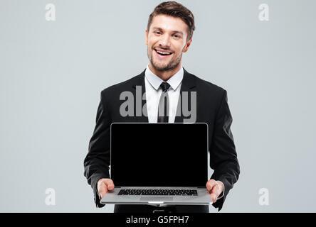 Happy young woman holding laptop écran vide sur fond blanc Banque D'Images