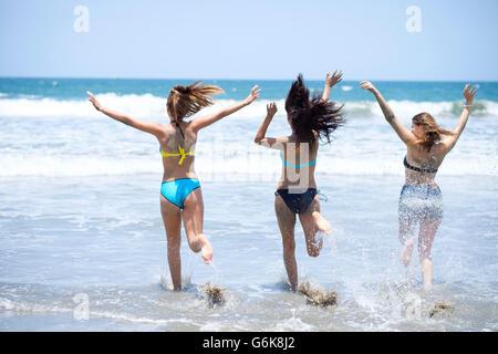 Trois amis s'exécutant dans la mer Banque D'Images