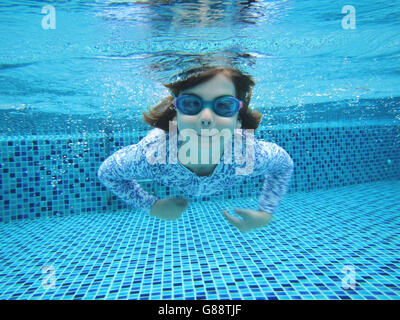 Girl swimming underwater in swimming pool Banque D'Images